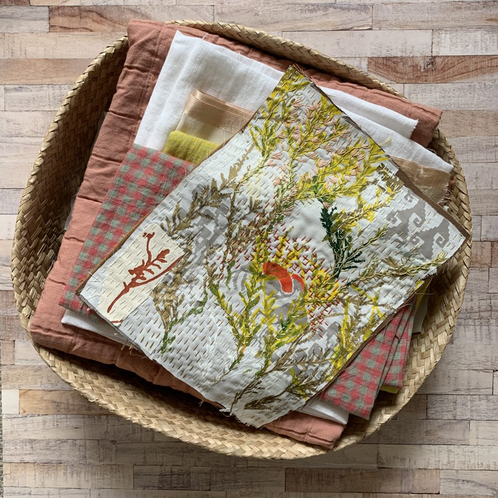 Swatches of folded orange, yellow and white fabric in a woven, shallow basket with a piece of embroidered fabric on top