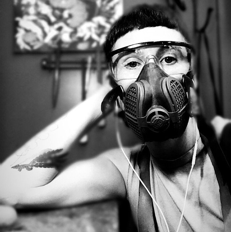 Seated artist wearing a respirator mask, clear glasses and headphones at a work bench in their studio, with tools and artwork on the wall behind