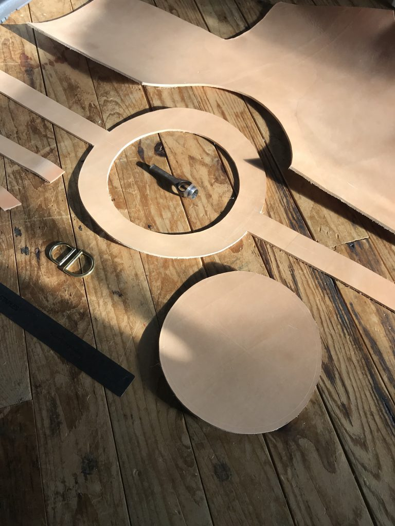 Handcut nude leather pieces with fixings laid out on wooden floorboards