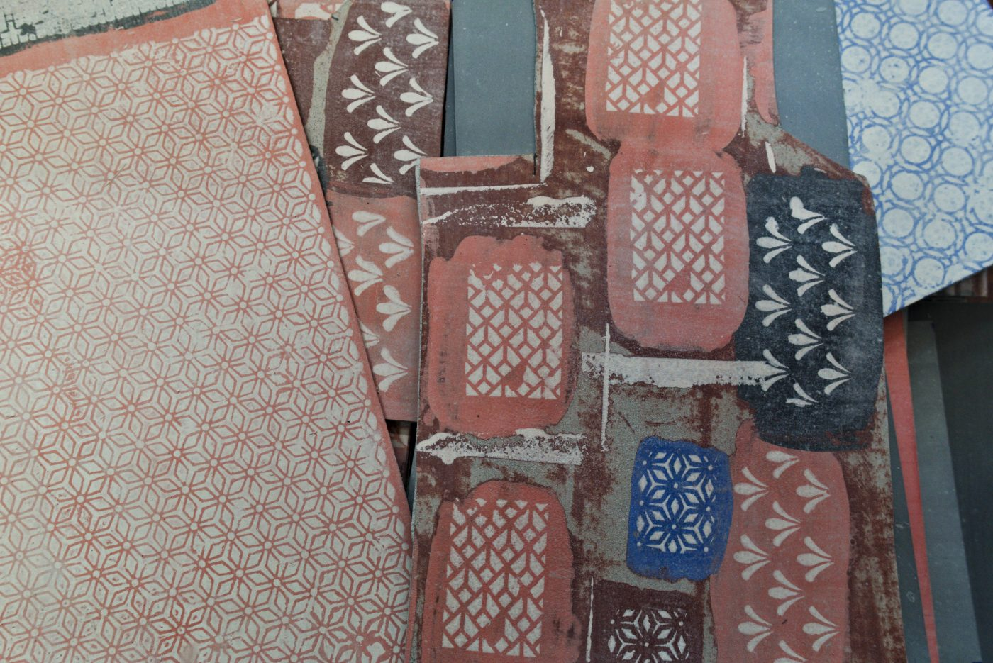 Large and small sheets of coloured porcelain card with white geometric patterns on top