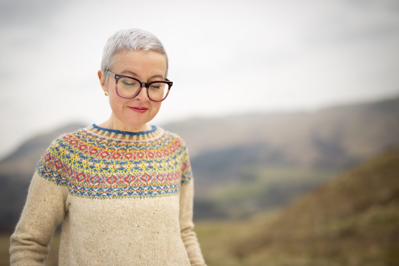 Female wearing glasses and a cream hand knitted jumper with a blue, red and yellow patterned yoke standing in the hills