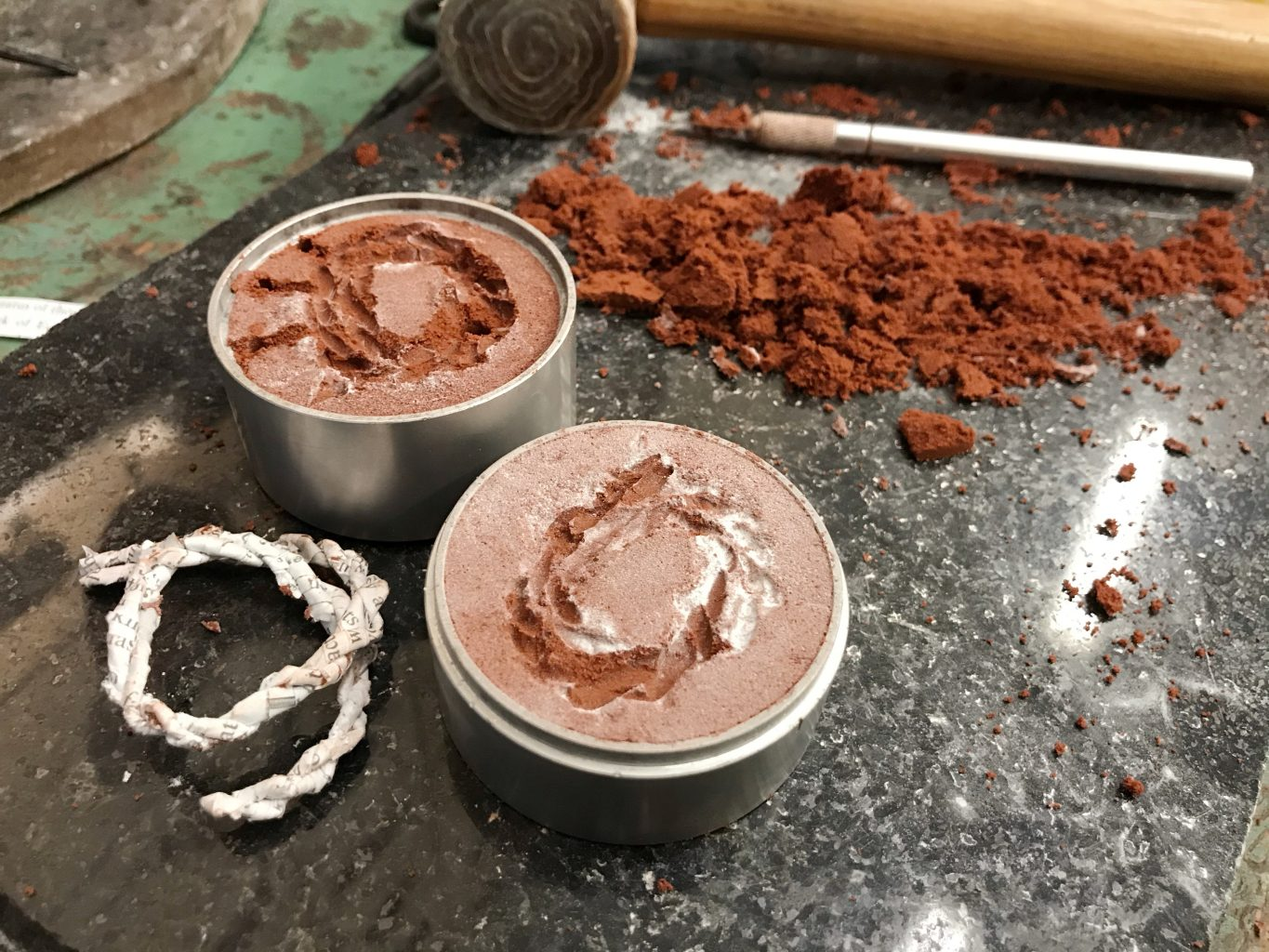 Two part metal tube filled with compacted, red sand, each with an impression of a piece of handmade paper rope, ready to cast in metal