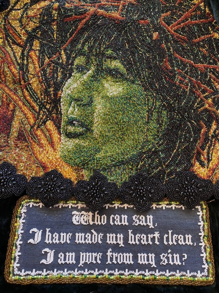 Detail of beaded cape, depicting a green face with a plaque below with text 'Who can say, I have made my heart clean, I am pure from my sin?'