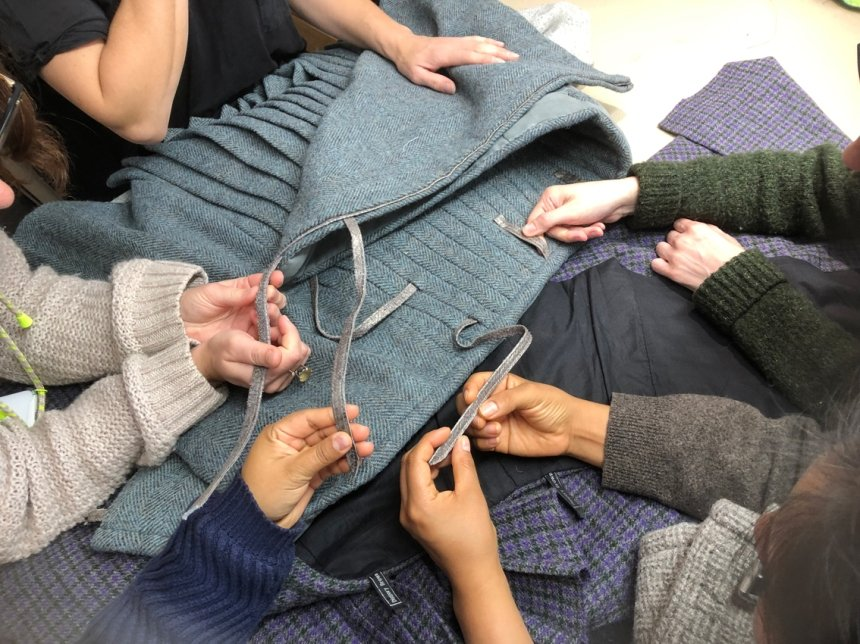 Five pairs of hands inspecting a kilt made of teal tweed and finished with fish skin ties, laid out on a table
