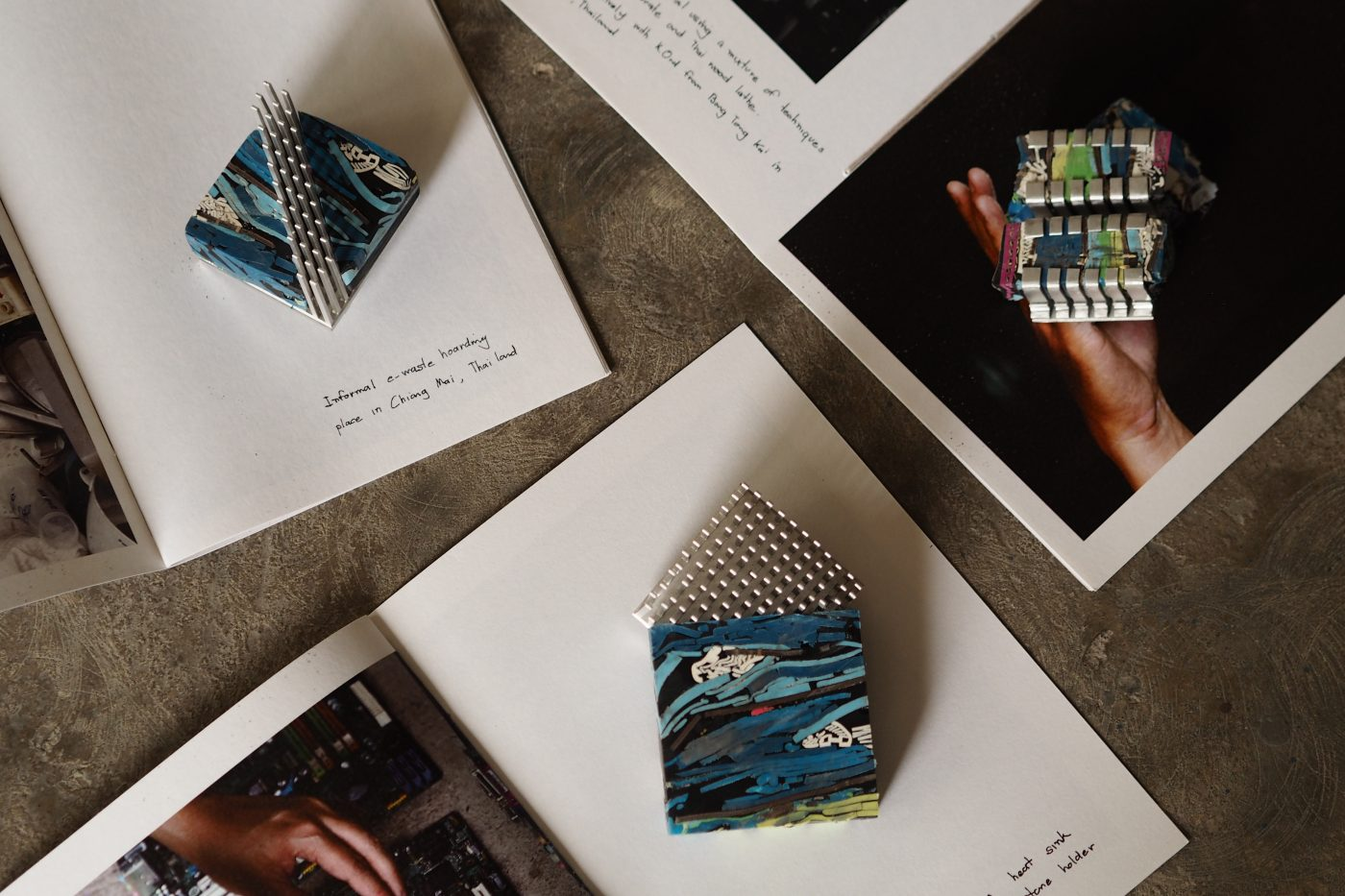 Small compositions of coloured, plastic composite material and metal alongside images of them, in notebooks with notes on the pages