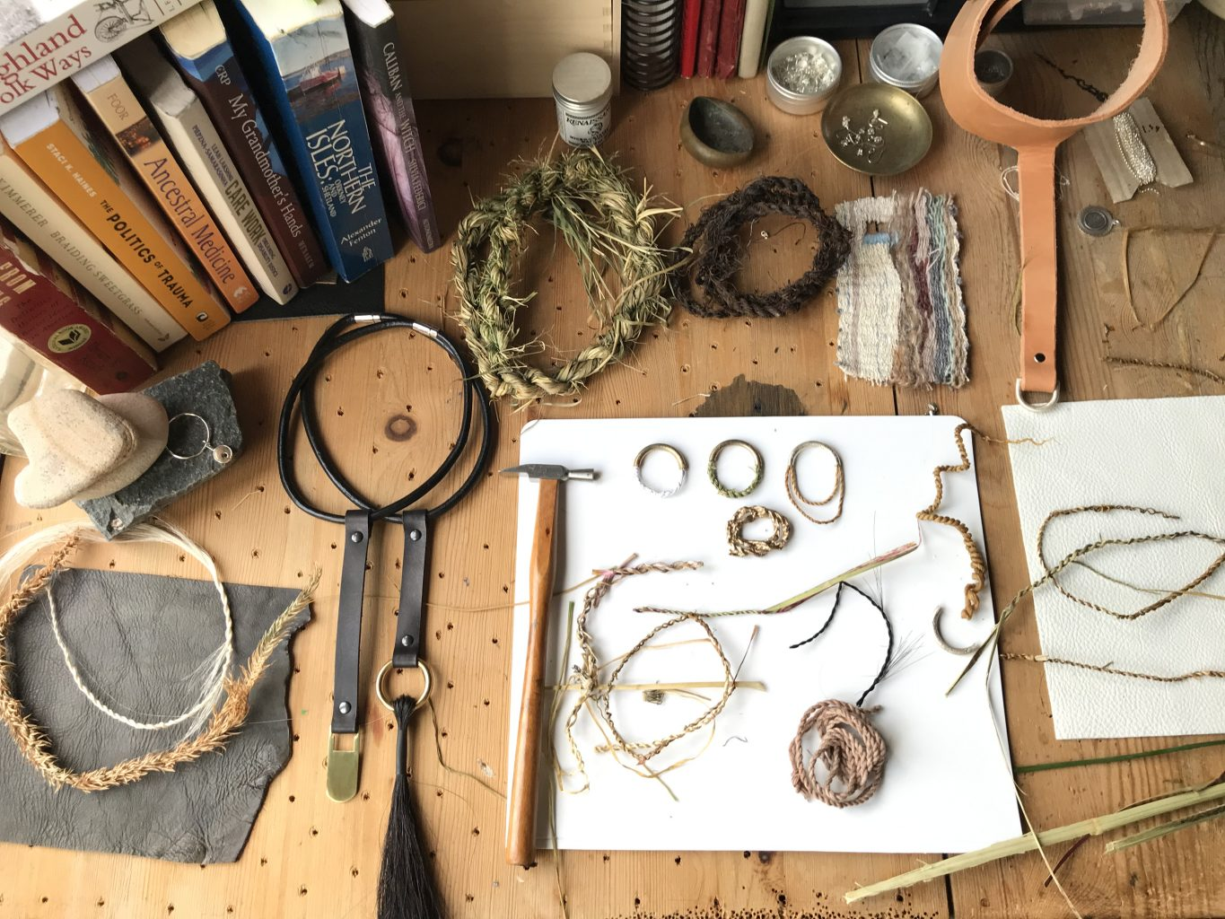 Bird's eye view of a workbench with handmade rope samples on a white sheet of paper, with cut leather and weaving samples, tools, found objects and books